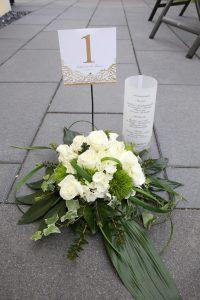 Weißer Blumestrauß zur Hochzeit mit goldener Tischnummer und Menükarte
