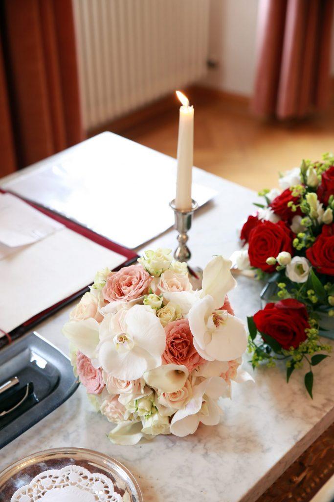 Blumenstrauß neben brennender Kerze
