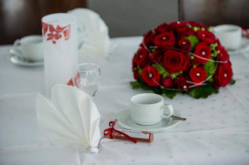 Blumen Tischgesteck in Rot neben einem Gastgeschenk