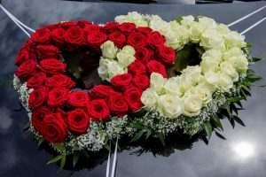 Auto Blumenschmuck in Form von zwei Herzen in weiß-rot auf einem schwarzem Mercedes