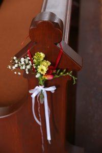 Blumenanhänger an Kirchenbank mit rotem Band
