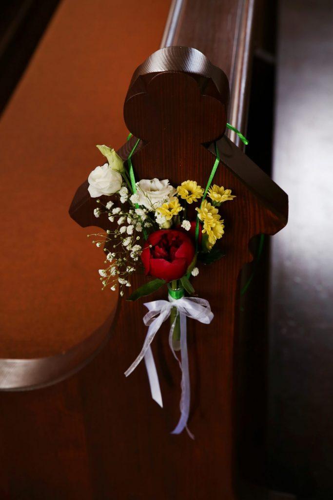 Blumenanhänger an Kirchenbank mit grünem Band