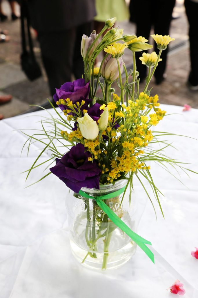 Blumen in Vase mit grünen Band