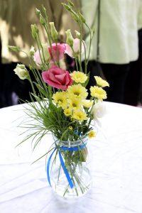 Blumen in Vase mit blauem Band