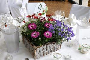 Blumenschmuck in Lila bepflanzt mit Tischnummer