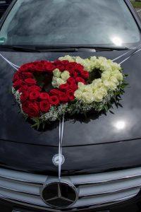 Autoblumenschmuck in Form von zwei Herzen in weiß-rot auf einem schwarzem Mercedes