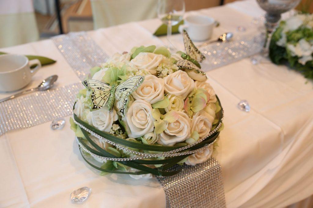 Tischgesteck aus weißen Rosen auf Glitzerbordüren