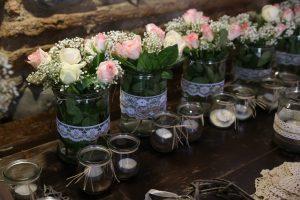 Blumengestecke in Vasen mit Spitzenband und Teelichtern
