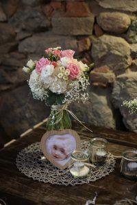 Blumenstrauss an Steinwand mit Teelichtern