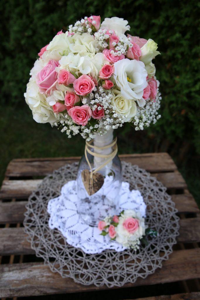 Blumenstrauss mit Rosa Rosen in Vase auf Holztisch mit vintage Tischdecke
