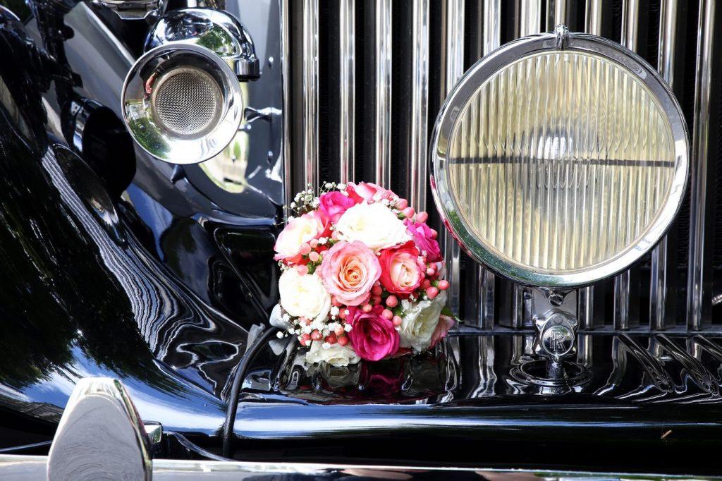 Brautstrauß im Kühlergrill eines Oldtimer