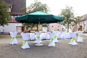 Großer Sektempfang mit Stehtischen, Hussen und Sonnenschirm in grün an der alten Kirche in Volkertshausen