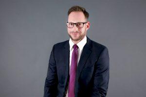 Bewerbungsfoto mit schwarzem Anzug mit Krawatte vor einem grauen Hintergrund