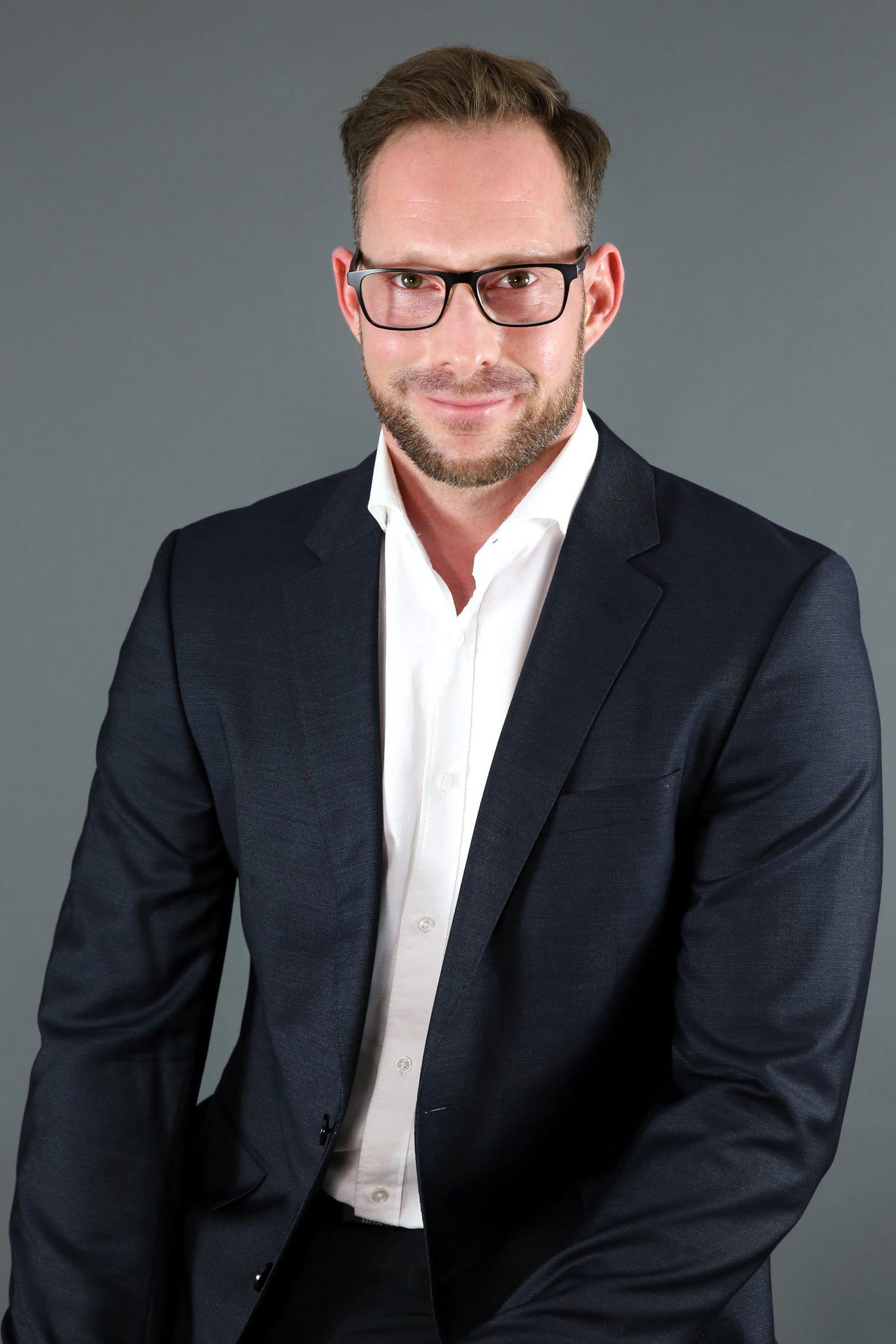 Bewerbungsfoto mit schwarzem Anzug vor einem grauen Hintergrund