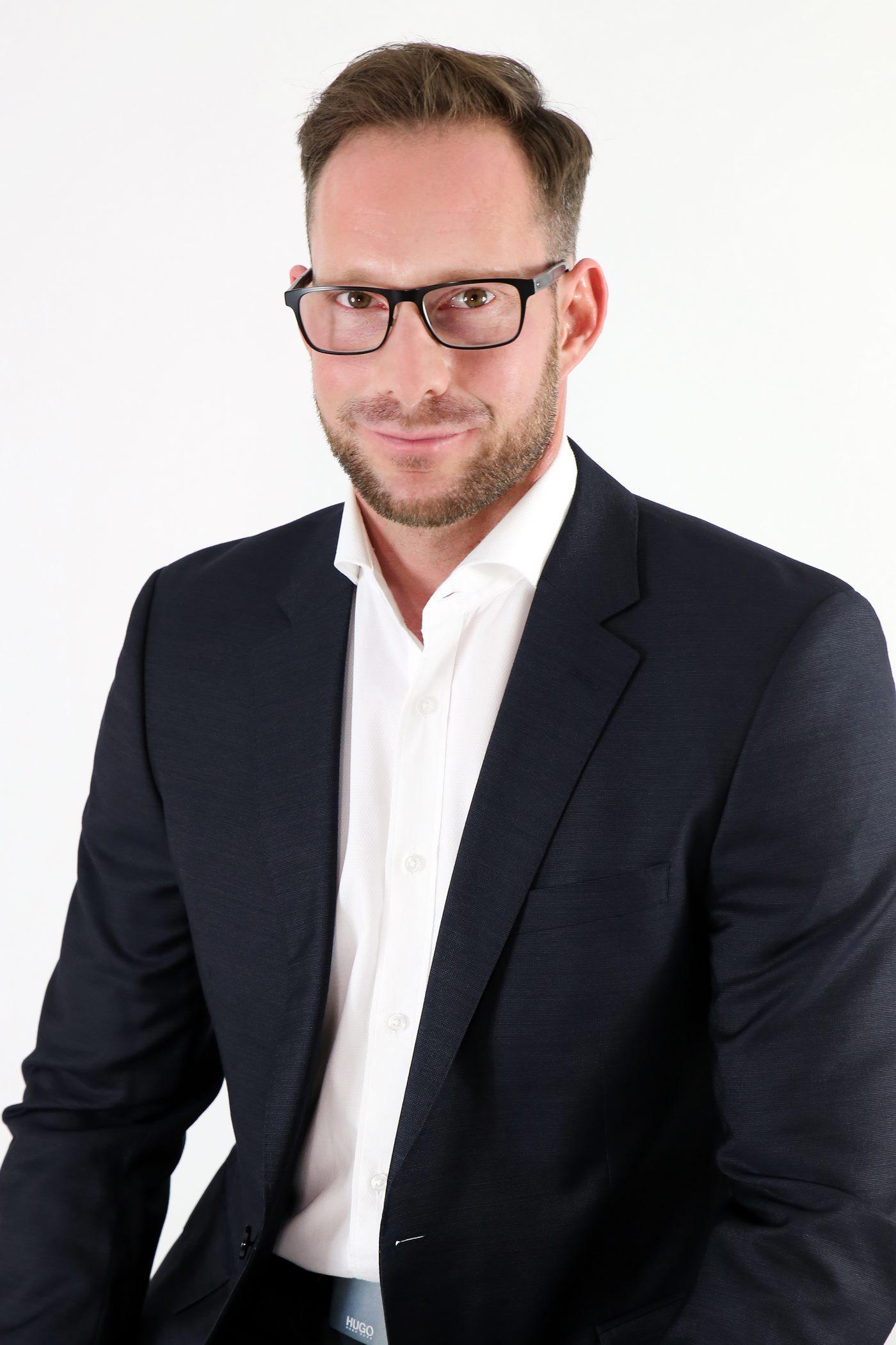 Bewerbungsfoto mit schwarzem Anzug vor einem weißem Hintergrund