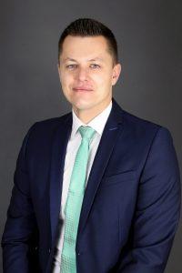 Bewerbungsfoto in blauem Anzug vor einem grauen Hintergrund