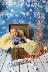 Baby fotografiert in Holzkiste zur Weihnachtszeit
