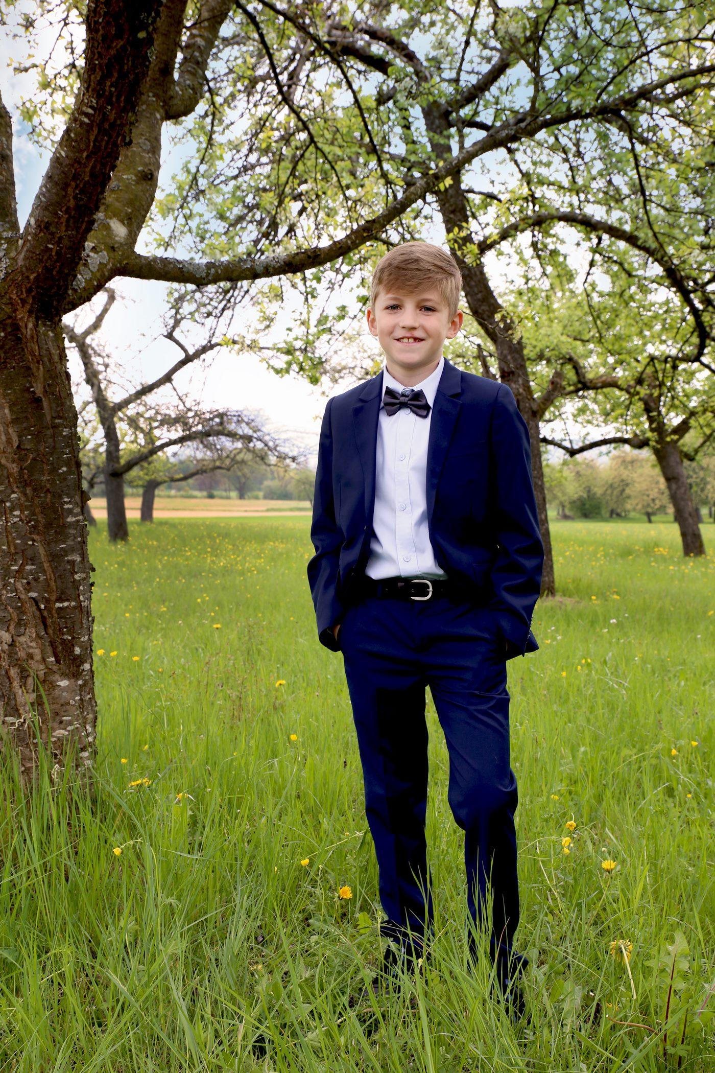 Junge am Baum bei seiner Kommunion unter einem Baum
