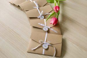 mehrere Pocketfold Einladungskarten mit weißem Satinband