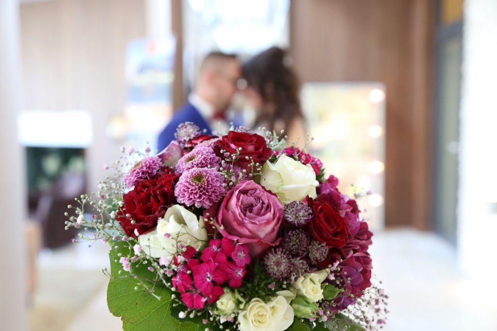 Brautstrauß nh mit Brautpaar im Hintergrund