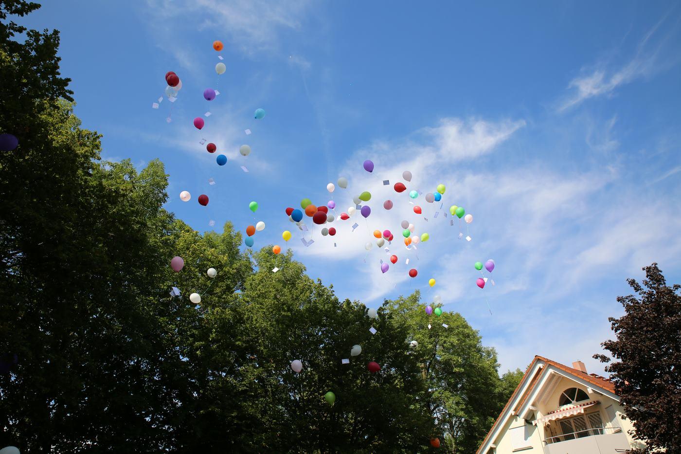 Bunte Ballons mit Grußkarten in der Luft fliegend