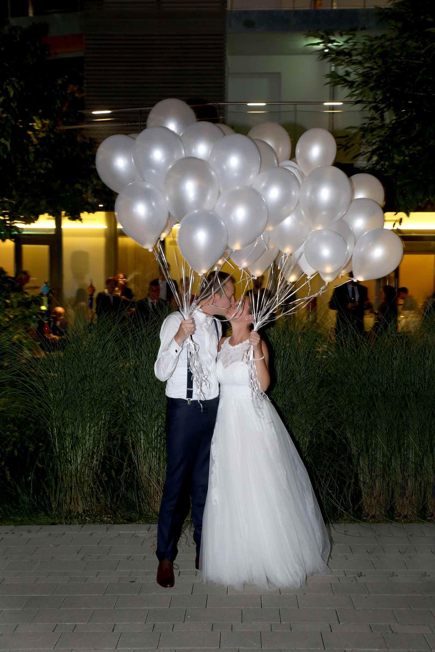 Helium Ballons in weiß vom Brautpaar gehalten