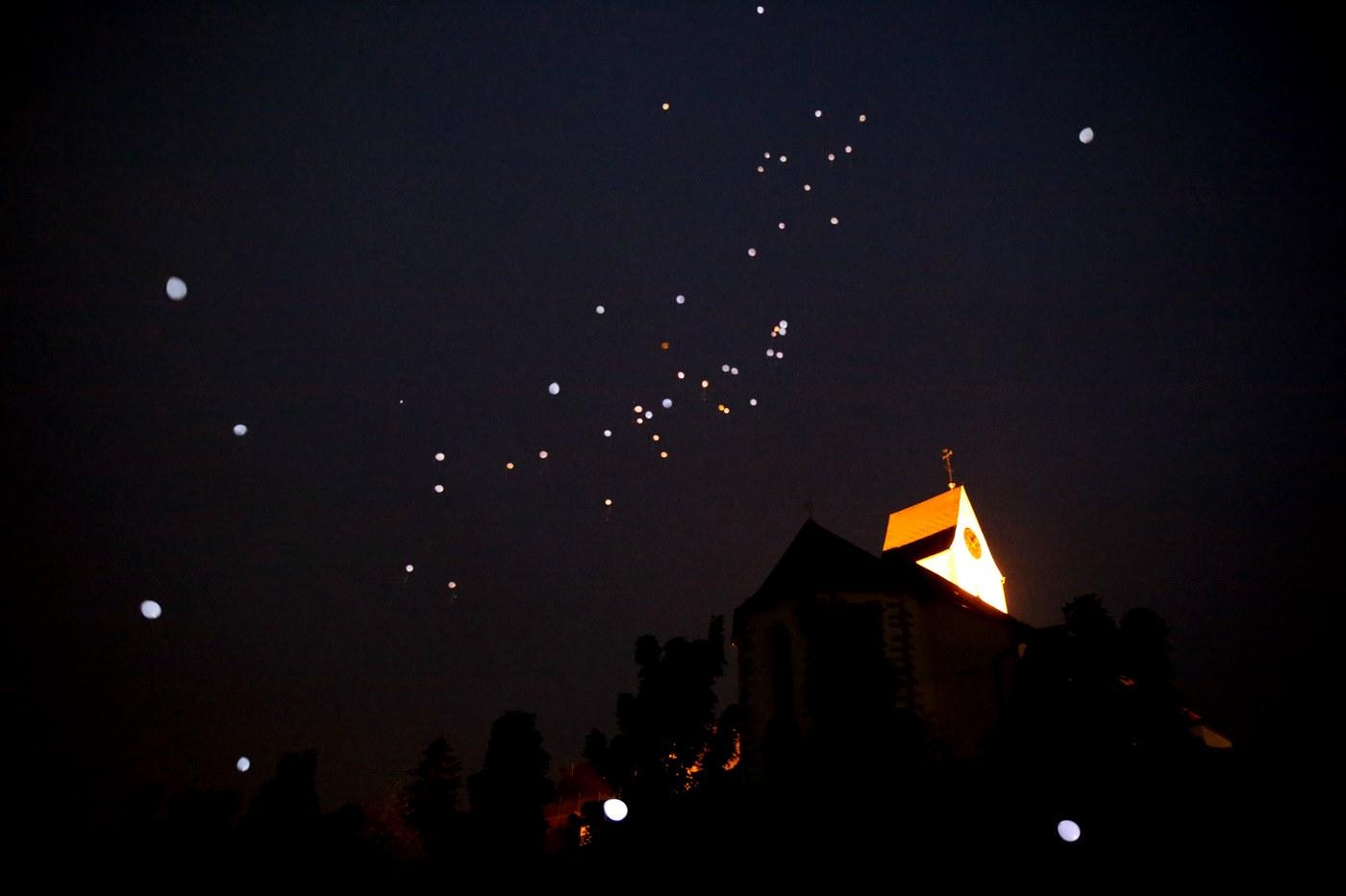 Weiße Helium Ballons bei Nacht