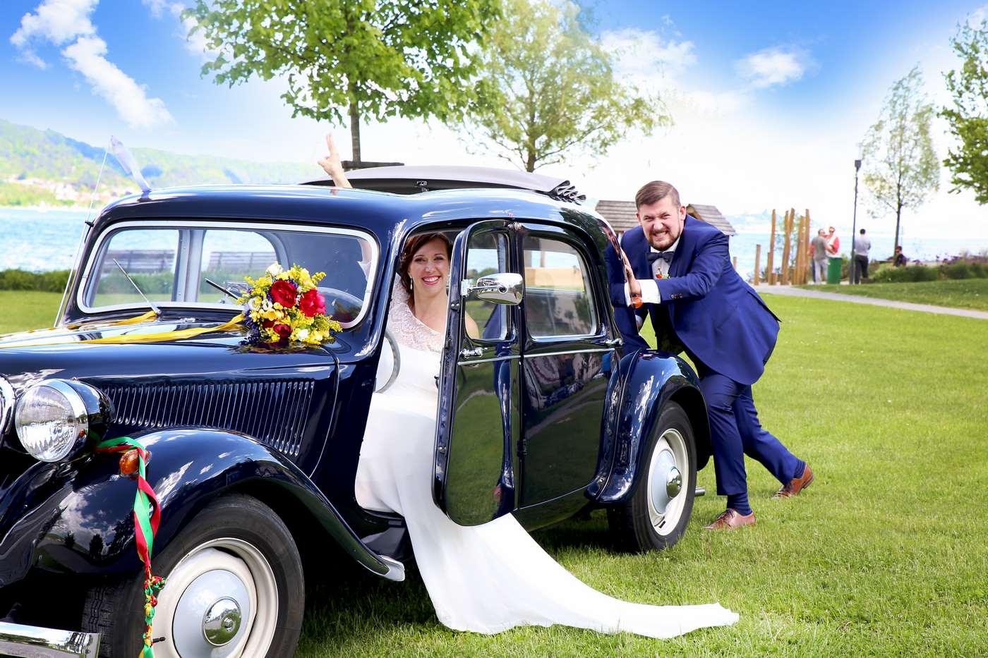 Bräutigam schiebt Braut im Hochzeitsauto an