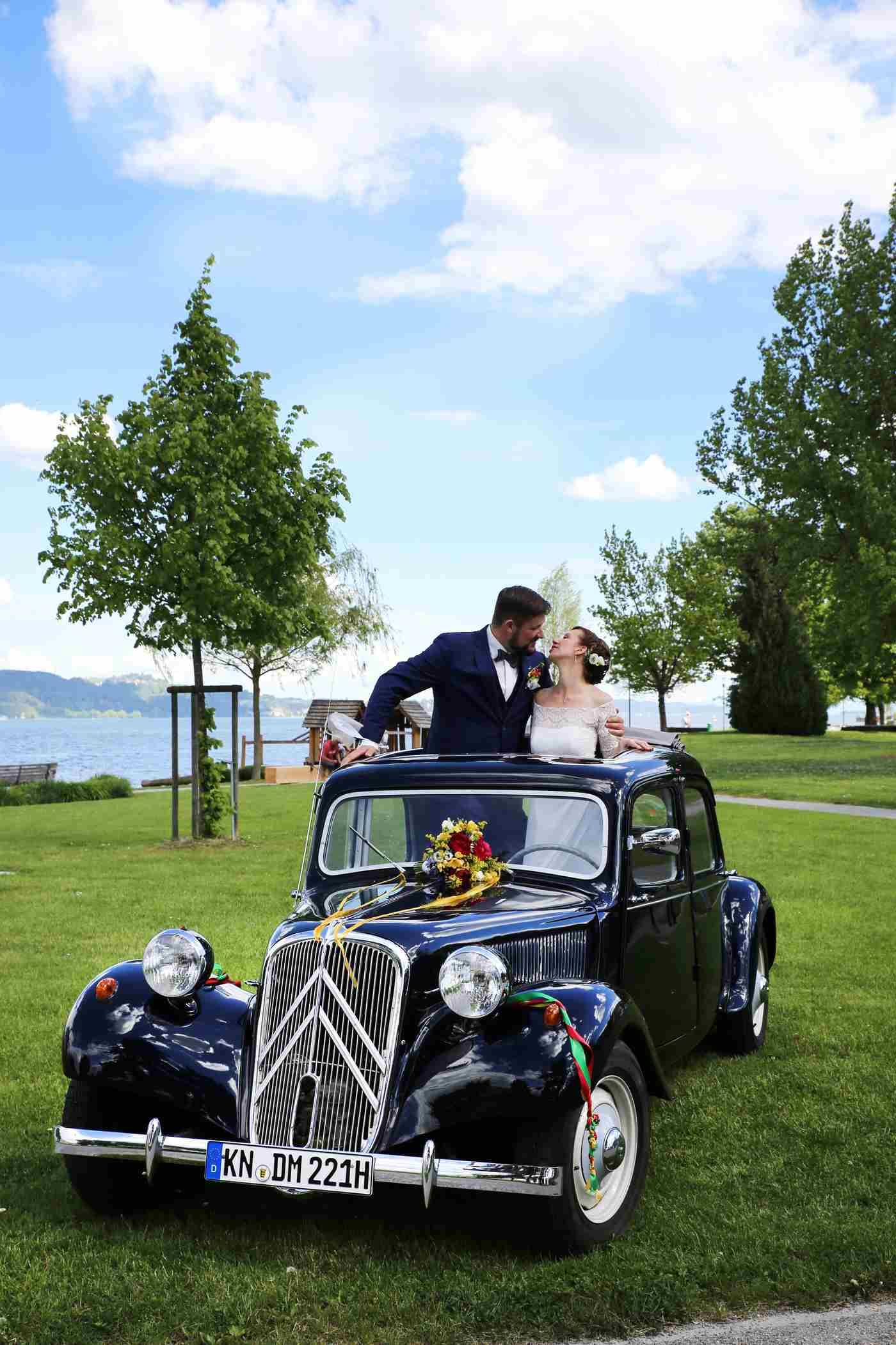 Brautpaar steht im Schiebedach vom Citröen Hochzeitsauto