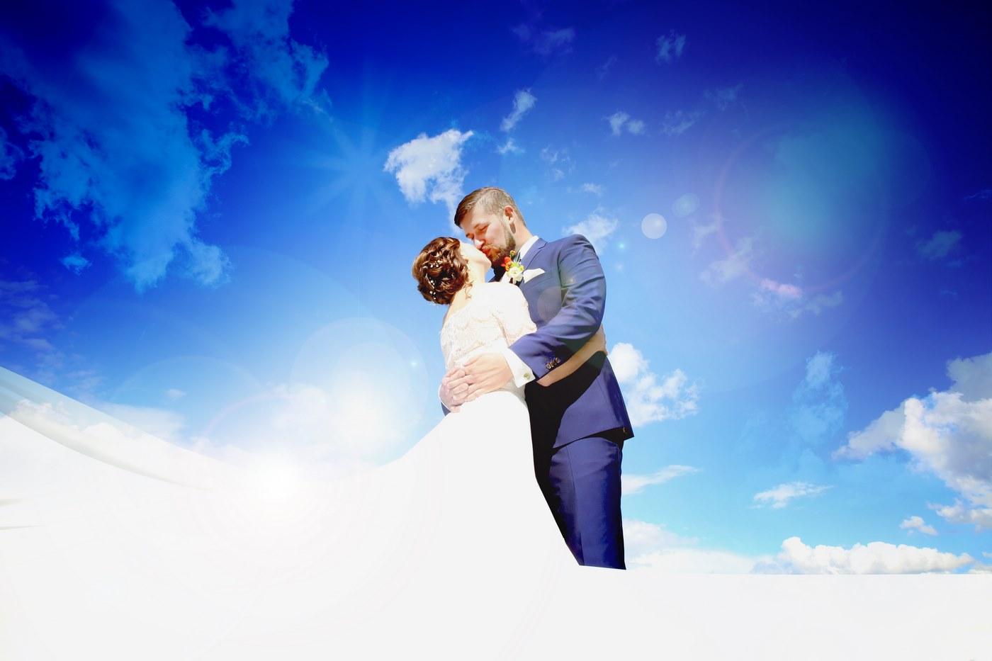 Küssendes Brautpaar vor strahlend blauen Himmel