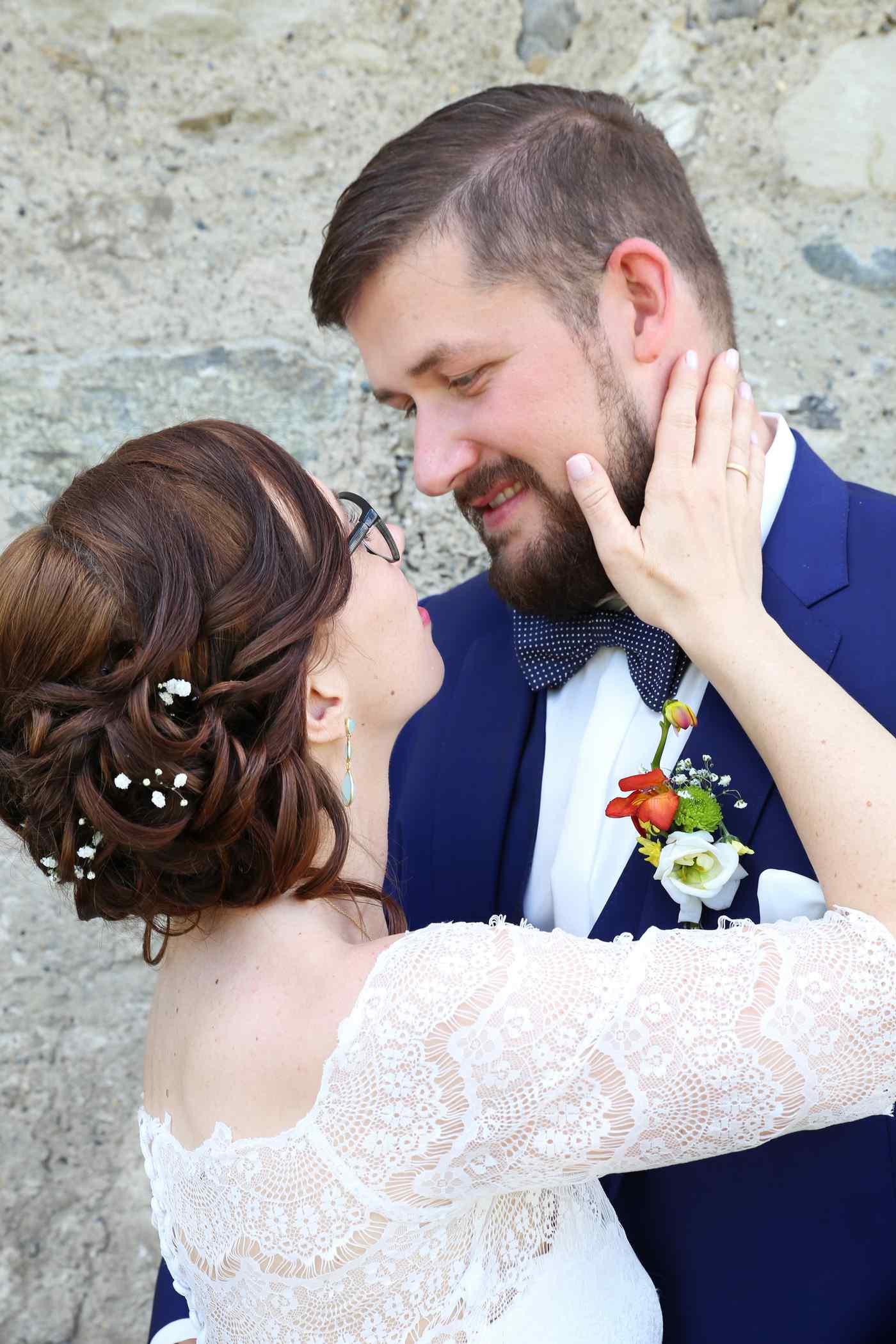 Braut hält Hand an Wange vom Bräutigam nah