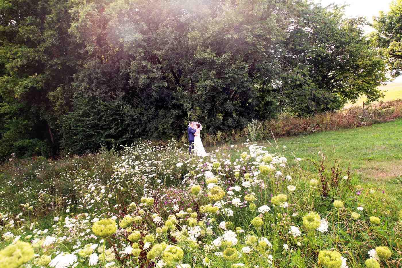 Brautpaar mit Schirm an Blumenwiese