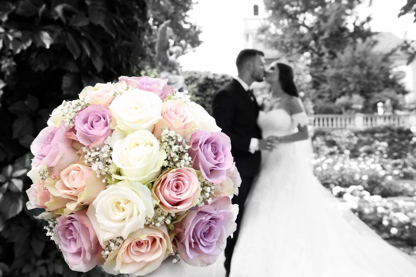 Brautpaar küssend hinter Brautstrauß