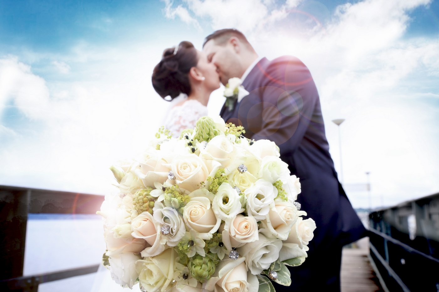 Brautpaar auf Holzsteg mit Blumenstrauß in der Hand