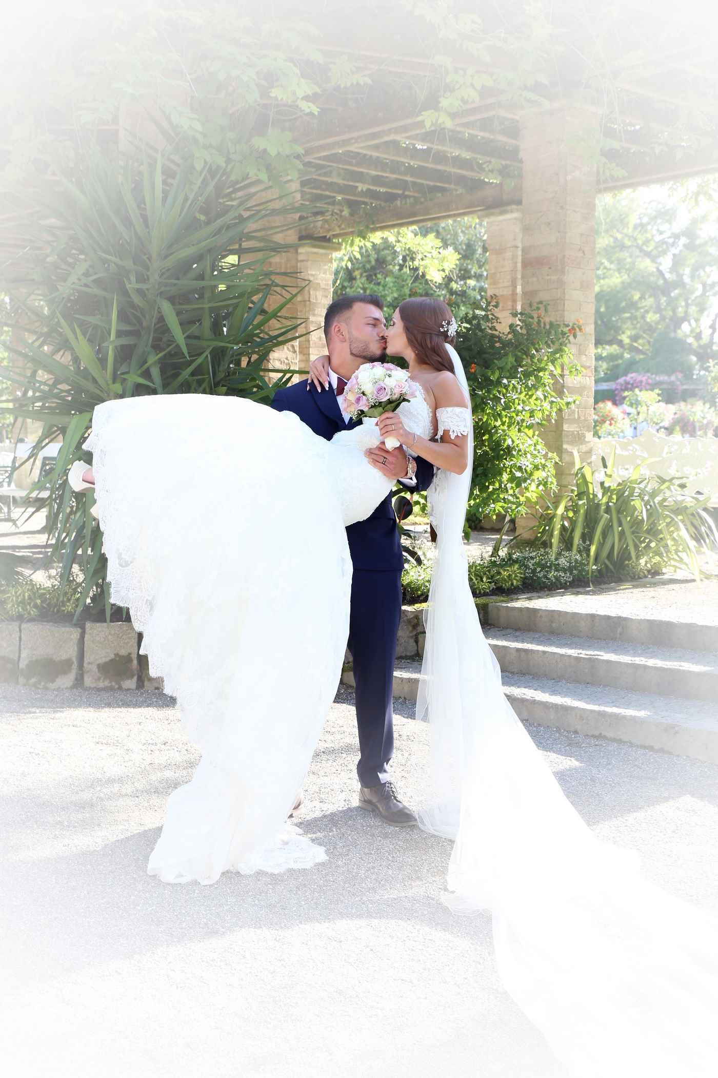 Bräutigam trät seine Braut in den Armen