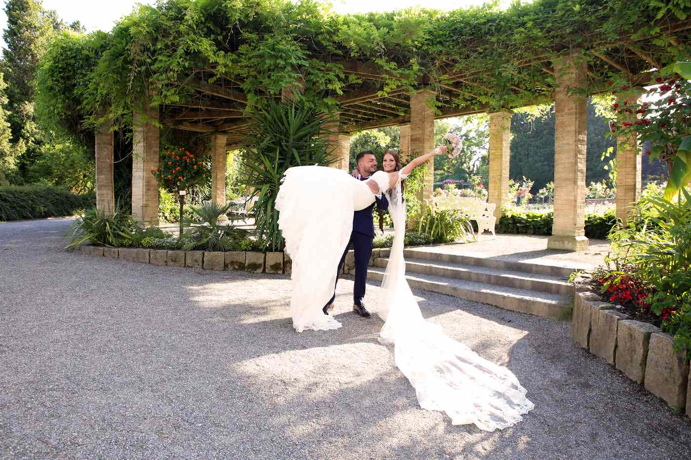 Bräutigam trät seine Braut in den Armen mit langem Schleier